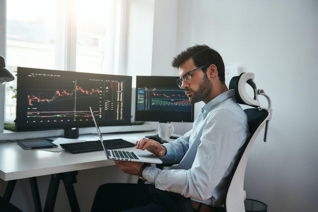 Bearded trader wearing eyeglasses analyzing financial market via laptop